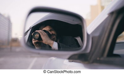 Reflection in side mirror of young private detective man...