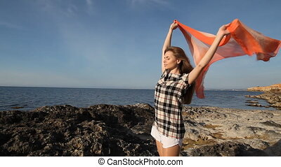 girl holds silk wind Beach rocks - girl holds silk develops...