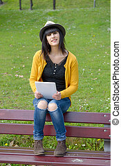 young brunette girlsitting on a bench with a tablet in park...