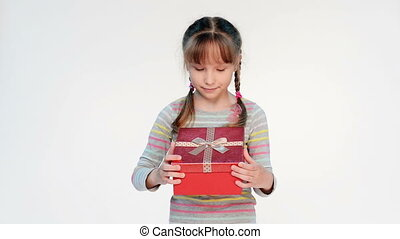 Little girl opening her gift feeling surprised embracing a...