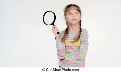 Little girl standing with magnifying glass, locked down real...