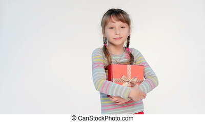 Little girl embracing red gift box, locked down real time...