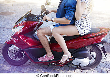 Close up of couple riding a scooter