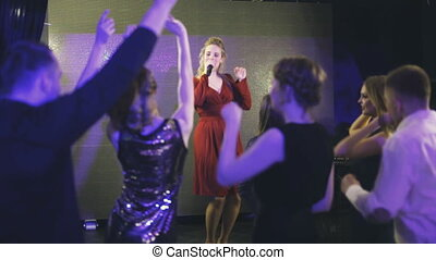 Beautiful singer is standing on stage and sings
