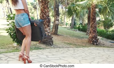 young brunette woman in shorts, sunglasses and heels carries...