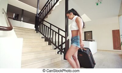 young brunette woman in shorts, sunglasses with suitcase up...