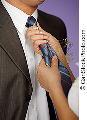 Woman straightens his tie - The woman straightens his blue...