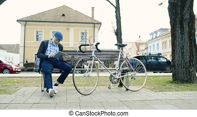 Senior man with bicycle in town, holding tablet, writing