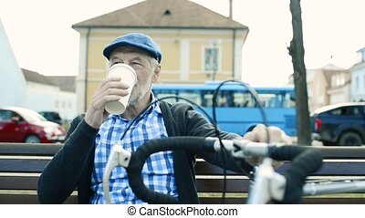 Senior man with bicycle in town drinking coffee.