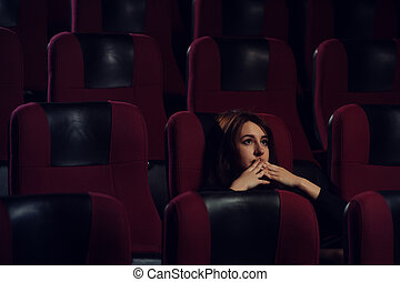 Young scared girl watching movie in cinema theater