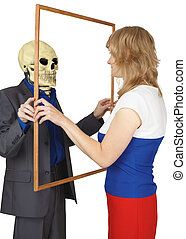 Woman looks at skeleton as reflected - A woman looks at a...