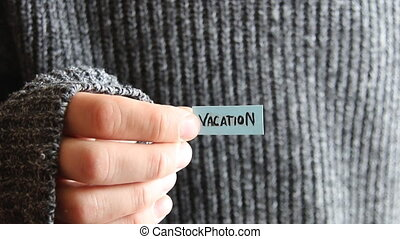 vacation - inscription on the tag - The guy holds a tag with...