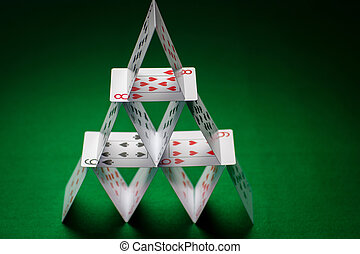 house of playing cards on green table cloth - casino,...