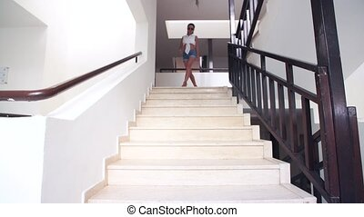young brunette woman in shorts, sunglasses down the stairs...