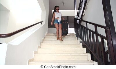 young brunette woman in shorts, sunglasses with suitcase...