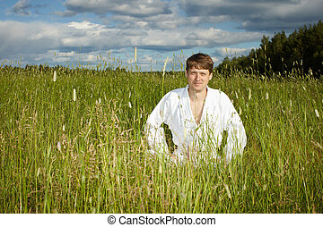 Young man in white kimono sits in grass