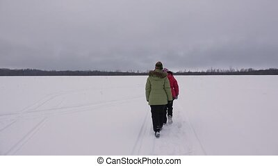 Girl walking in winter field. 4K.