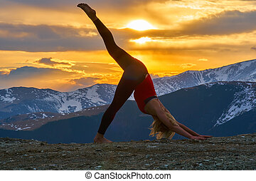 Young woman doing yoga in the mountains