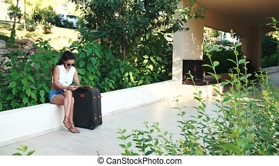 young tanned brunette woman in shorts, sunglasses with suitcase sitting and talking on phone in summer.