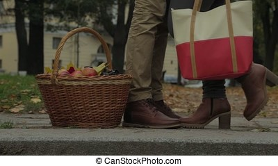 Couple in outdoor with picnic basket, kissing. Woman raises...