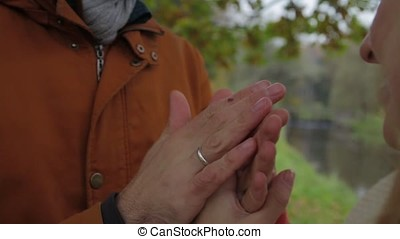 A man warms woman's hands. Bride and groom holding hands and warm each other in a park. Man and woman holding hands. warming hands.