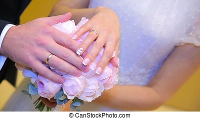 Newly wed couple's hands with wedding rings. Bride and groom with wedding rings on flowers or wedding bouquet. Newly wed couple's hands with wedding rings