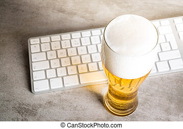 Beer next to computer keyboard on concrete table - Beer next...