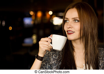 Beautiful young girl sipping coffee