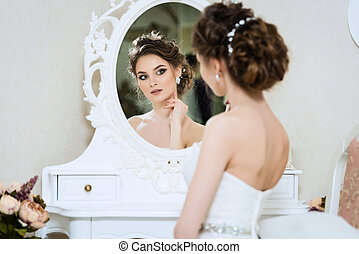 Beautiful young bride in front of the mirror. Portrait with wedding makeup, hairstyle, dress