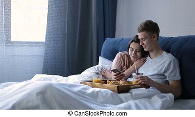 Joyful lovers having breakfast in bed at home