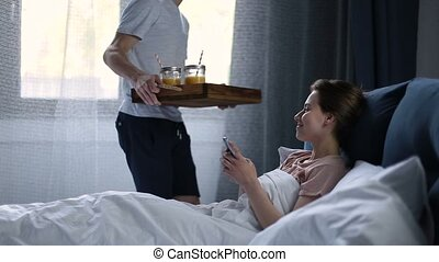 Smiling couple having breakfast in bed in morning - Handsome...