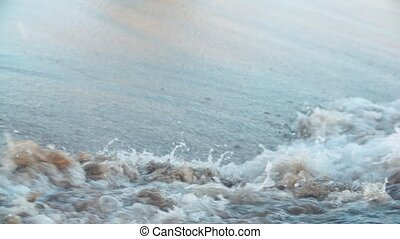 wave of the sea on beach at sunset close up