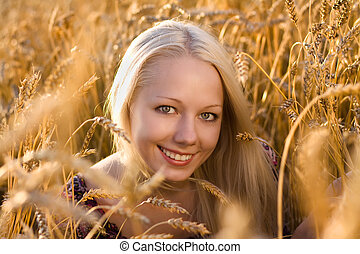 beautiful blonde woman smilling at the wheat field closeup