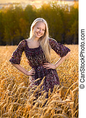 beautiful blonde woman in dress smilling at the wheat field