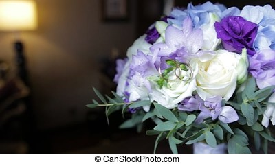 Wedding rings on a bouquet of white flowers. wedding rings and bouquet of dark blue flower. Close up. Wedding