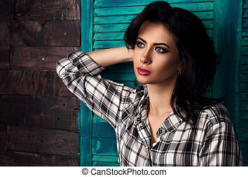 Beautiful makeup woman in trendy black and white checkered shirt relaxing thinking on blue wooden doors background. Short hairstyle