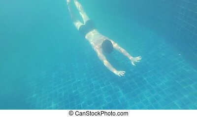 happy guy swims with enjoyment under the water in the pool