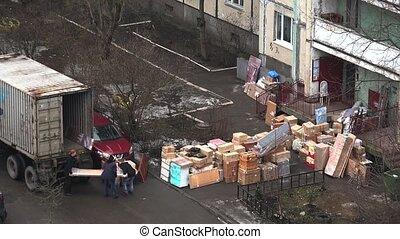 Workers unload items from the van. 4K. - SAINT-PETERSBURG,...