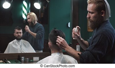 Male barber combing hair at the hairdresser. Hair styling