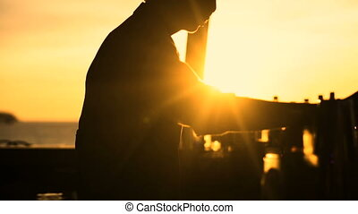 Silhouette of barman preparing cocktail at sunset outside at...
