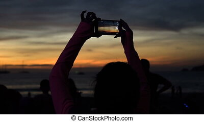 Silhouette of woman taking picture of sunset with phone at beach