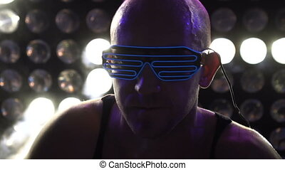 Man dancing at the party wearing neon led glasses - Closeup...