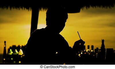 Silhouette of barman preparing cocktail at sunset outside