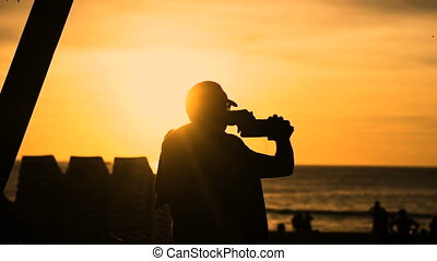 Silhouette of man standing on beach taking selfie photo during sunset