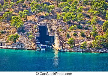 Boat and submarine shelter on Brac island stone coast,...