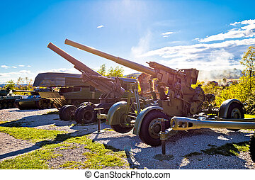 Military tanks and cannons with sun rays view