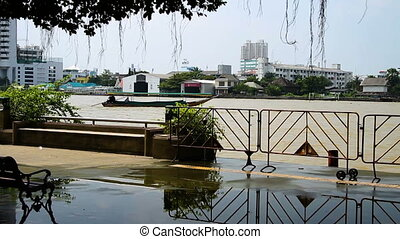 Chao Phraya river embankment. Boat shakes on waves. Bangkok,...