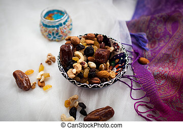 plate with nuts and dried fruits lying on a white table