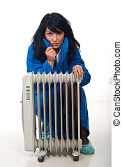Woman shivering in house - Woman shivering and sitting near...