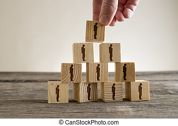 Human resources - Man stacking a tower of wood blocks with...